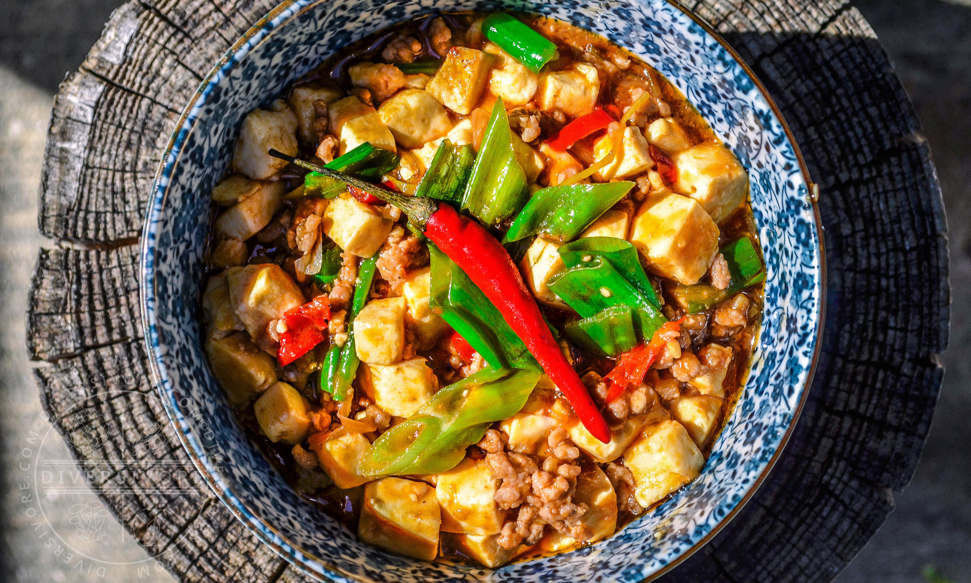 Mapo tofu in a blue and white bowl, topped with a red chili pepper