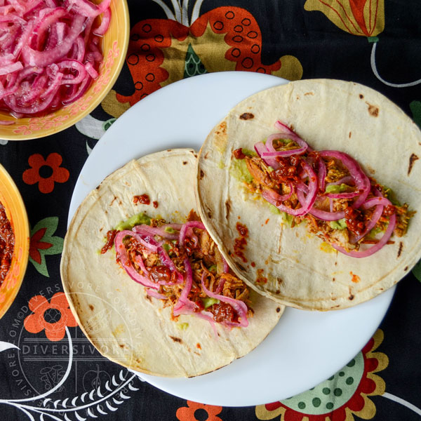 Pressure-cooked Puerco Pibil with pickled onions and guacamole, served in tortillas, flanked by smoky dried chili salsa