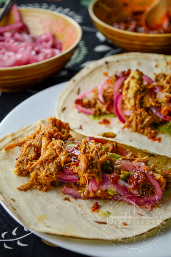 Pressure-cooked Puerco Pibil with pickled onions served in tortillas, flanked by smoky dried chili salsa and pickled onions in bowls