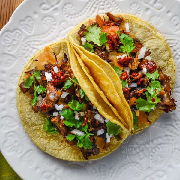 Instant Pot Carnitas con Queso served in corn tortillas with onions and spicy dried chili salsa