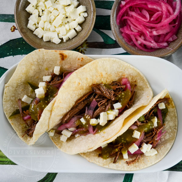 Shredded beef brisket with pasilla-morita adobo, fresh cheese, and pickled red onions