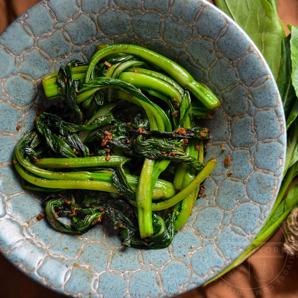 Stir-fried choy sum in a decorative ceramic bowl