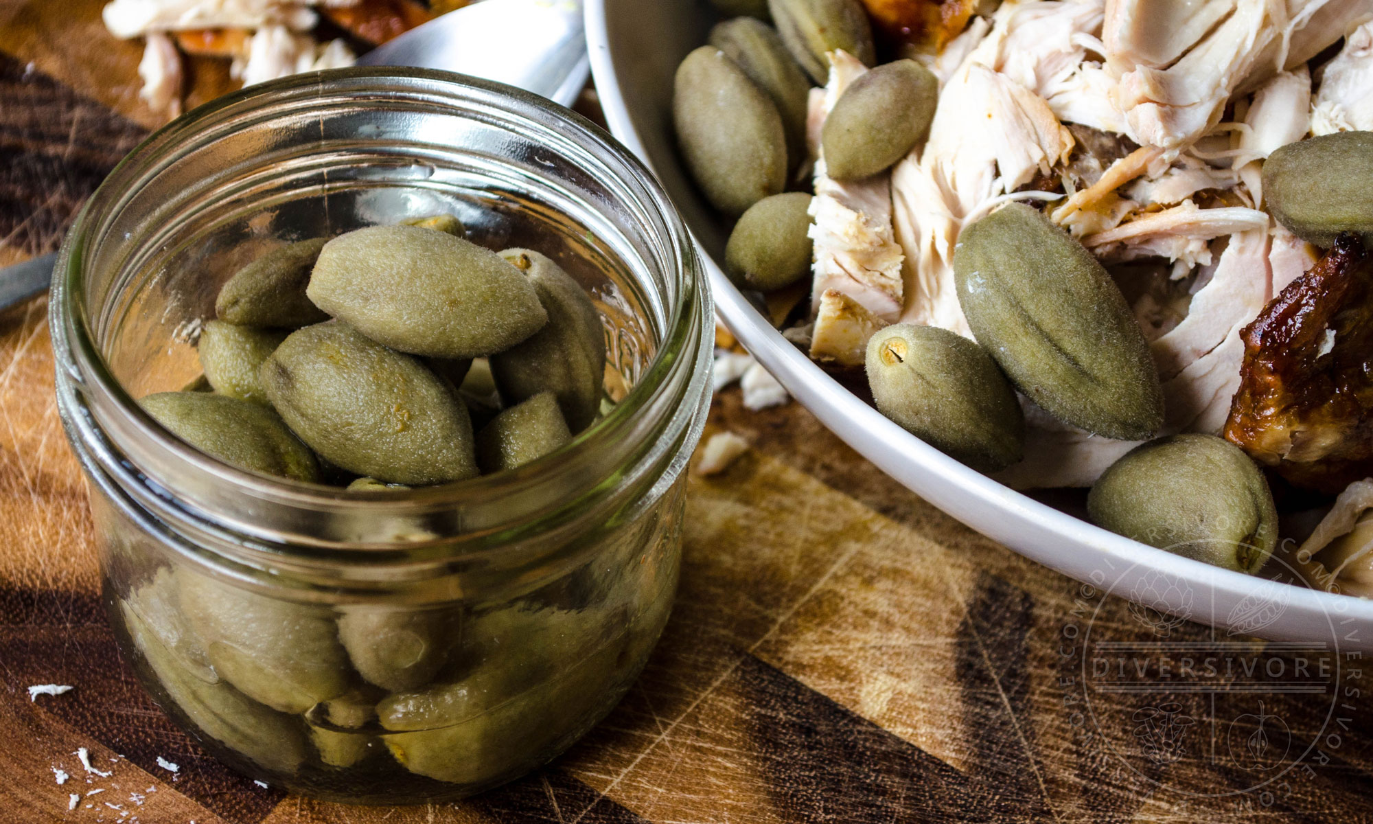 Pickled green almonds in a glass mason jar in front of a plate of chicken