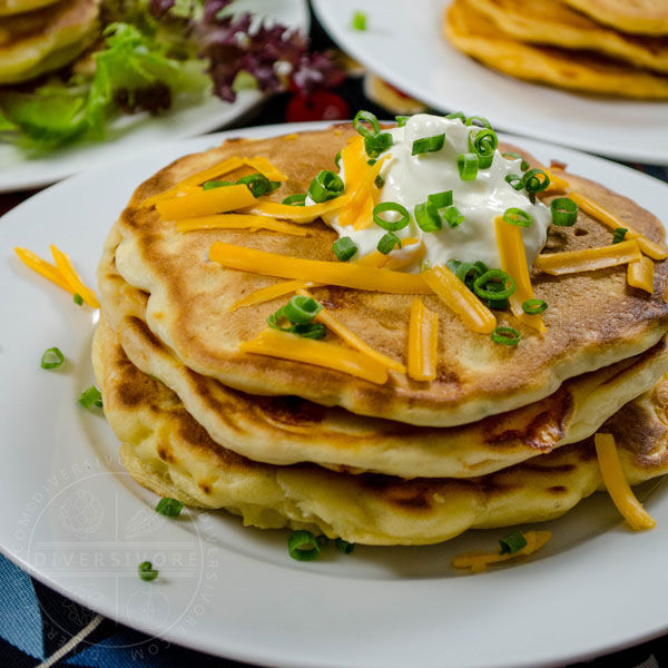 Bacon, cheddar, and chive pancakes topped with sour cream, cheese, and chives, all served on a white plate