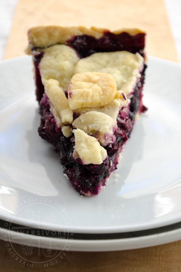 A slice of cherry-blueberry pie on a white plate