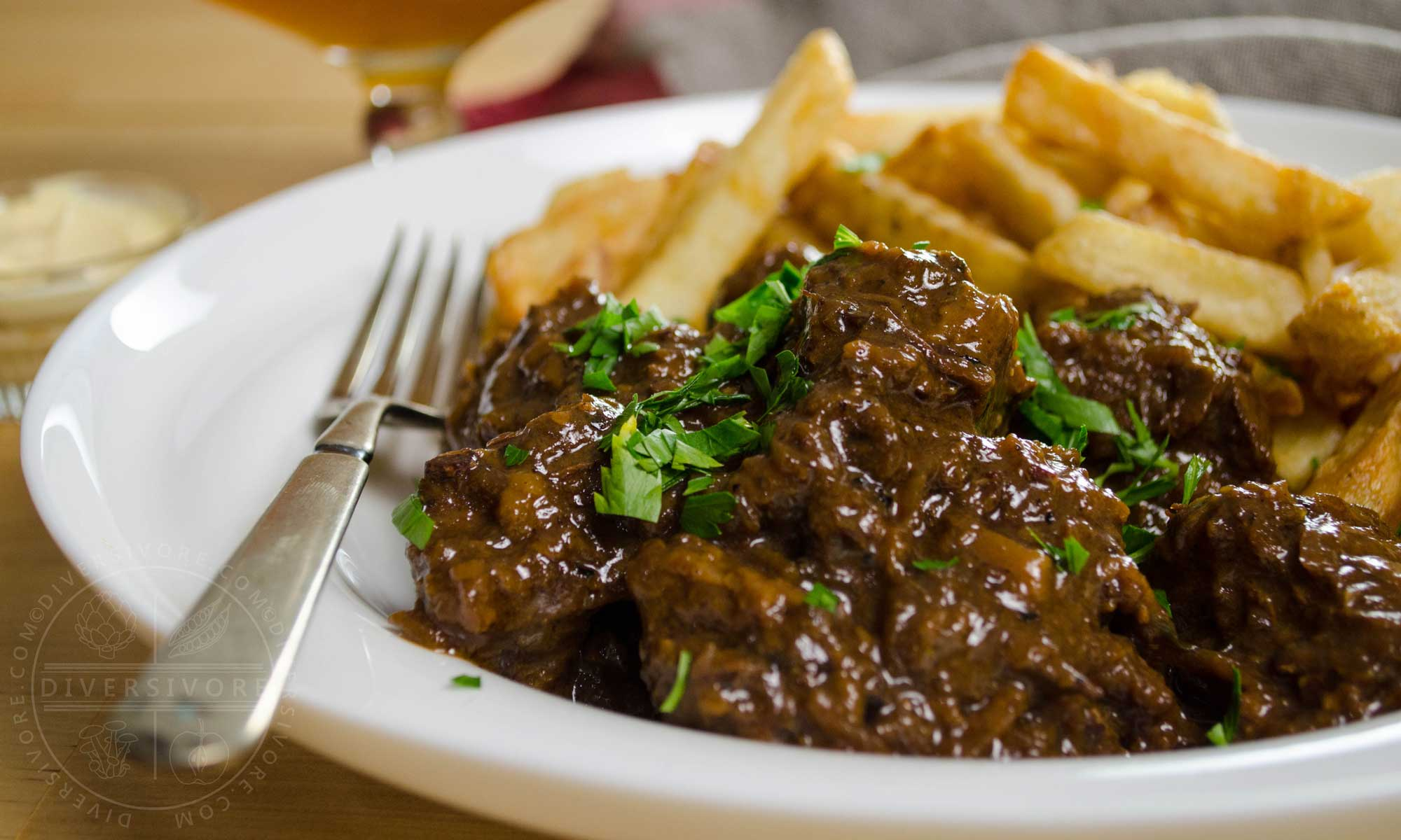 Carbonnade - Flemish Beef and Beer Stew in a white bowl with fries and a silver fork