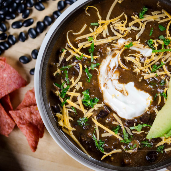 A bowl of Chili Mole with avocado, sour cream, and shredded cheese