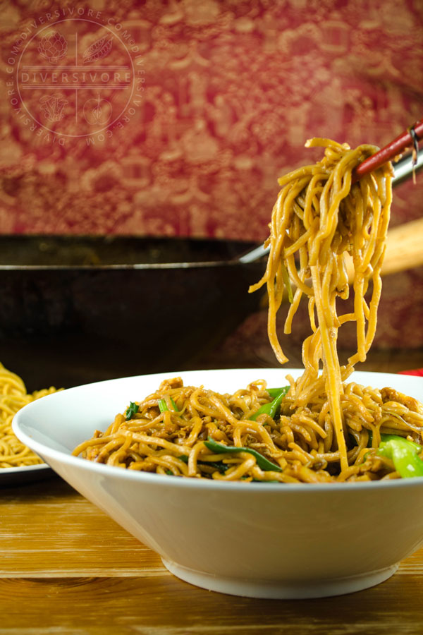 Chopsticks holding soy sauce fried noodles above a bowl