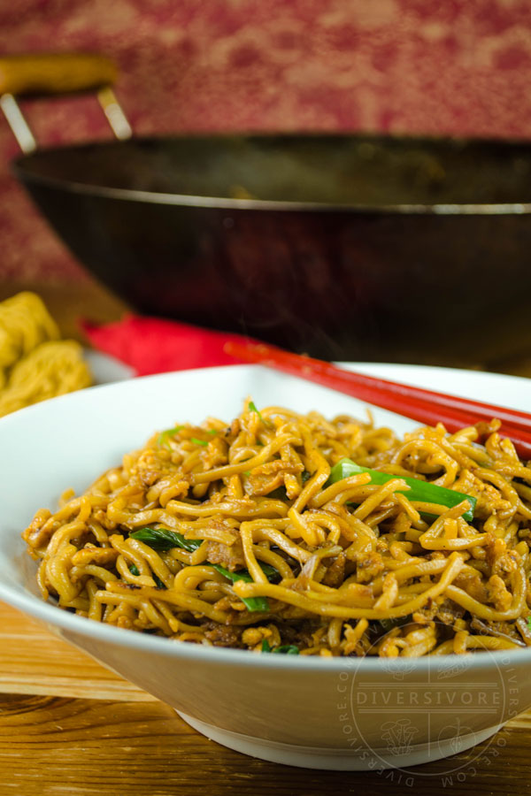 Soy sauce fried noodles in a white bowl with red chopsticks