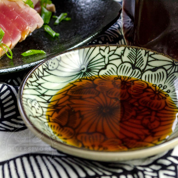 Ponzu shoyu in a small dish beside seared tuna tataki