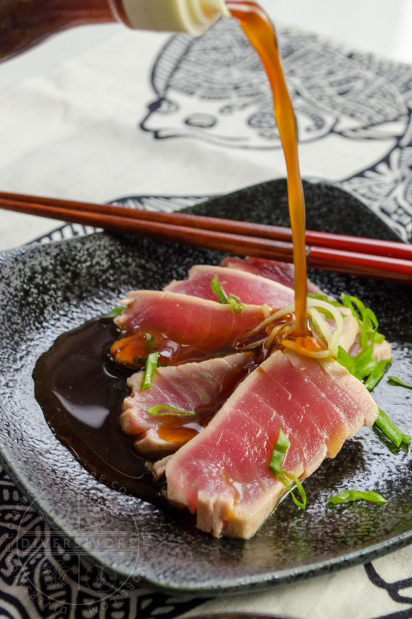 Ponzu shoyu being poured onto tuna tataki in a small dish