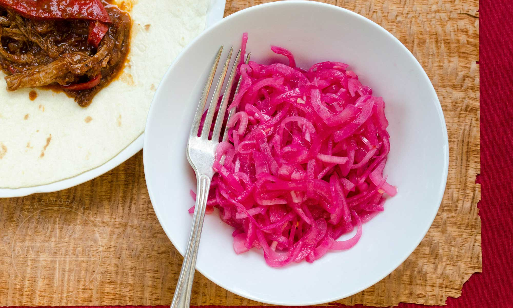 Mexican Pickled Red Onions in a white bowl, shown with a silver fork