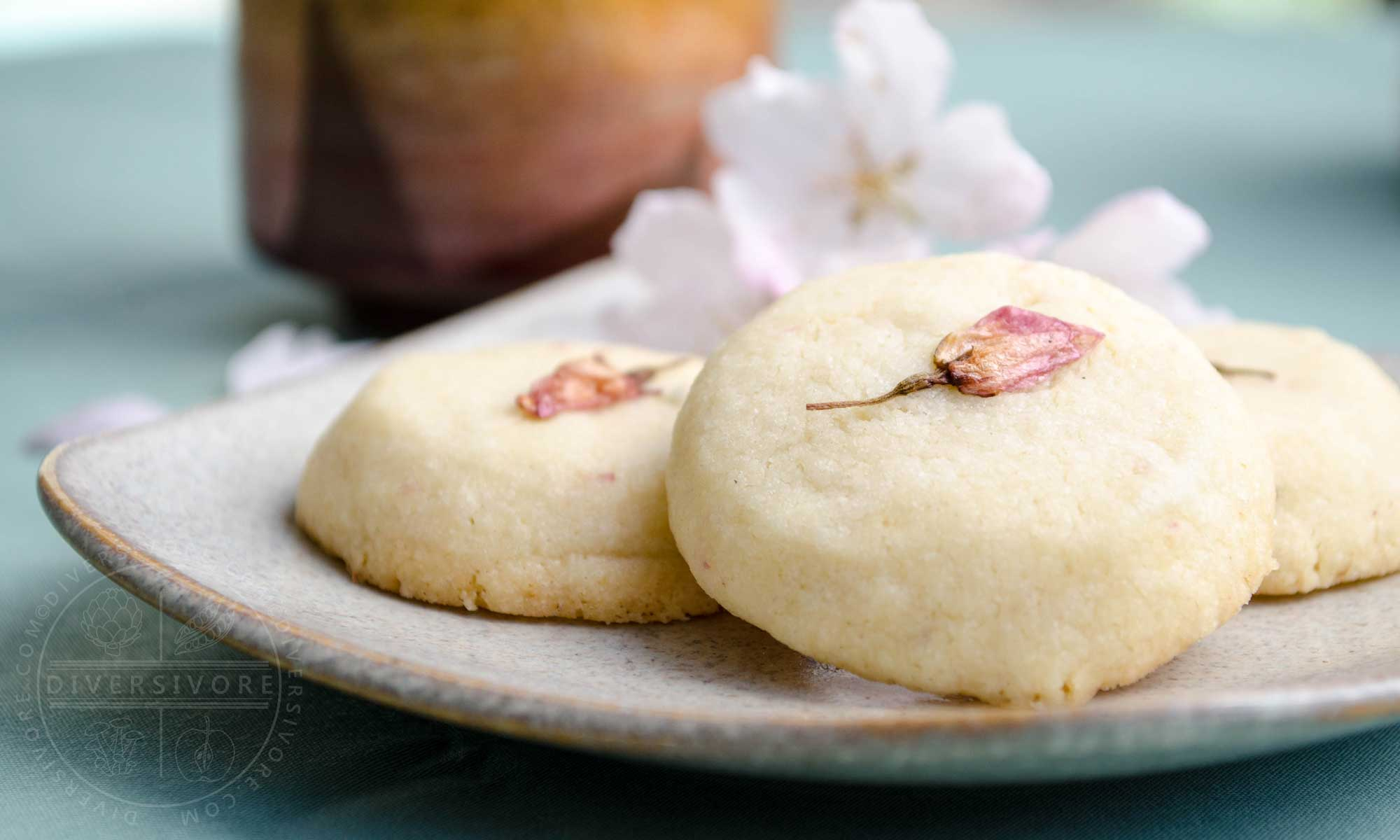 Sakura Sabure - Cherry blossom shortbread cookies on a sand-coloured plate with a tea cup
