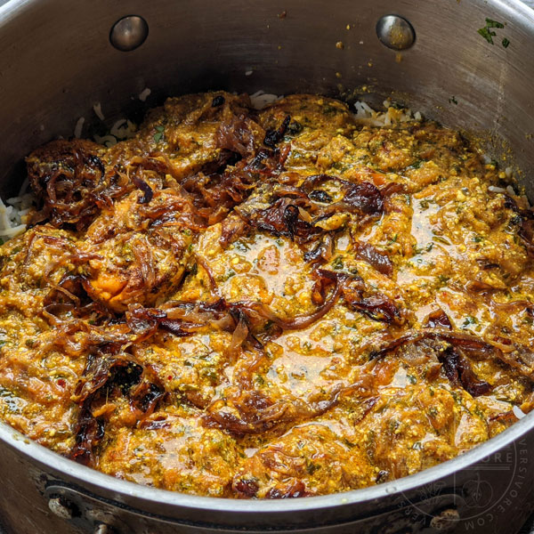 Hyderabadi egg biryani layered with gravy and fried onions, ready for another layer of rice